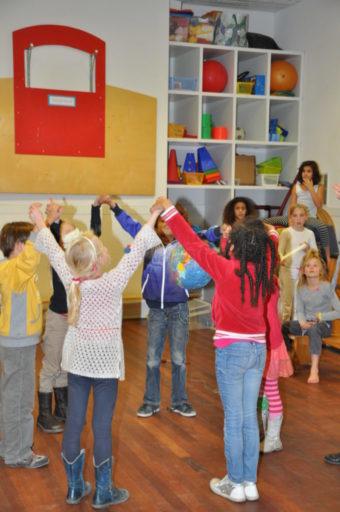 Kinderen in een kring met armen omhoog